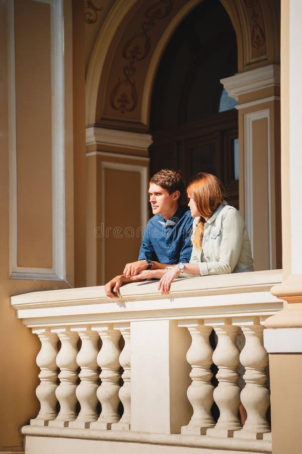 逗人喜爱的年轻美好的行家夫妇旅行的欧洲,站立在歌剧院阳台 免版税库存照片