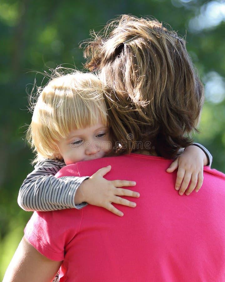逗人喜爱的幼儿拥抱她的妈妈 免版税库存照片