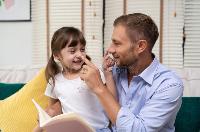 逗人喜爱的微笑女孩和她英俊的父亲使用与鼻子和在家一起坐沙发 ?????` s? 免版税库存照片