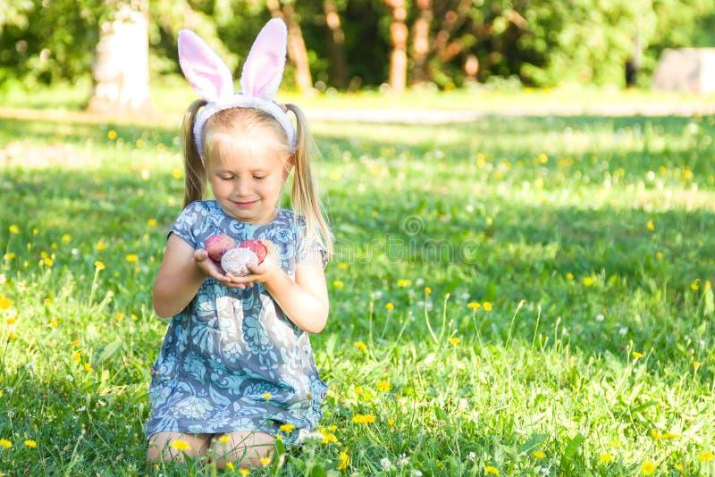 逗人喜爱的微笑的女孩佩带的兔宝宝耳朵在复活节天 坐草和拿着被绘的复活节彩蛋的女孩 库存照片