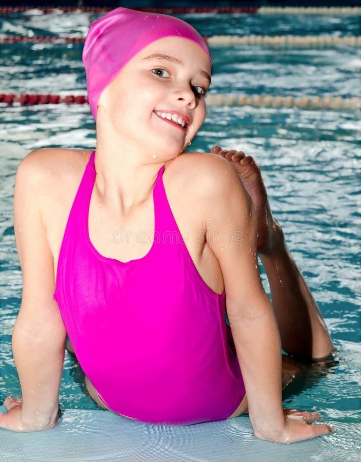 逗人喜爱的微笑的女孩儿童游泳者画象桃红色游泳衣和盖帽的在游泳场 库存图片