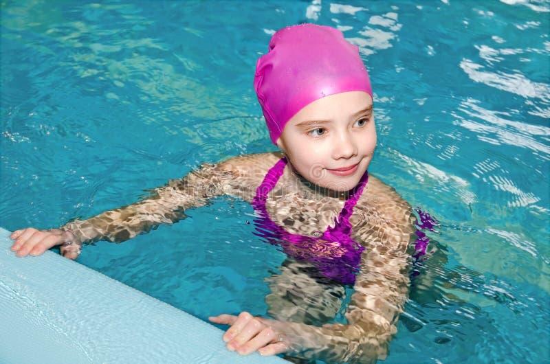 逗人喜爱的微笑的女孩儿童游泳者画象桃红色游泳衣和盖帽的在游泳场 免版税图库摄影