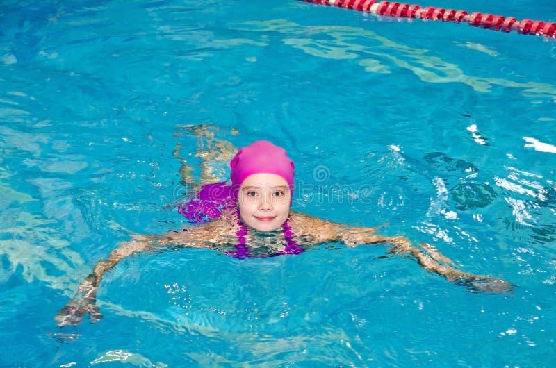逗人喜爱的微笑的女孩儿童游泳者画象桃红色游泳衣和盖帽的在游泳场 免版税库存图片