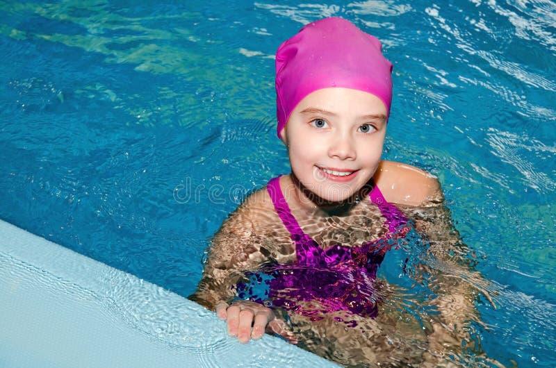 逗人喜爱的微笑的女孩儿童游泳者画象桃红色游泳衣和盖帽的在游泳场 库存照片