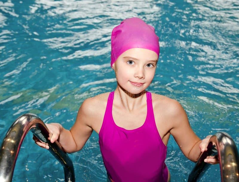 逗人喜爱的微笑的女孩儿童游泳者画象桃红色游泳衣和盖帽的在游泳场 免版税库存照片