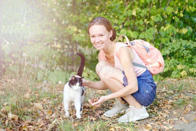 逗人喜爱的微笑的女孩冲程在街道上的一只发出愉快的声音的猫 黑白颜色 无家可归的动物 图库摄影