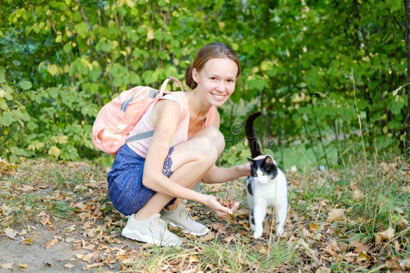 逗人喜爱的微笑的女孩冲程在街道上的一只发出愉快的声音的猫 黑白颜色 无家可归的动物 库存照片