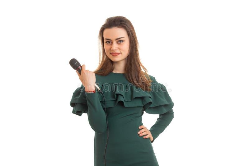 逗人喜爱的微笑的女孩在演播室在她的手上站立并且拿着一个话筒 免版税库存照片