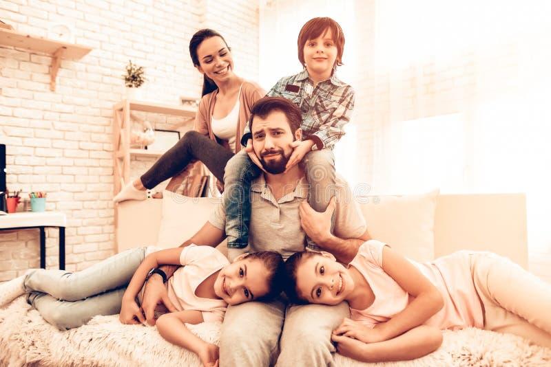 逗人喜爱的微笑的家庭画象坐沙发 库存图片