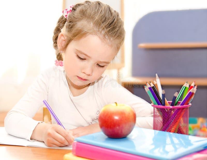 逗人喜爱的微笑的小女孩书写在书桌 免版税库存图片