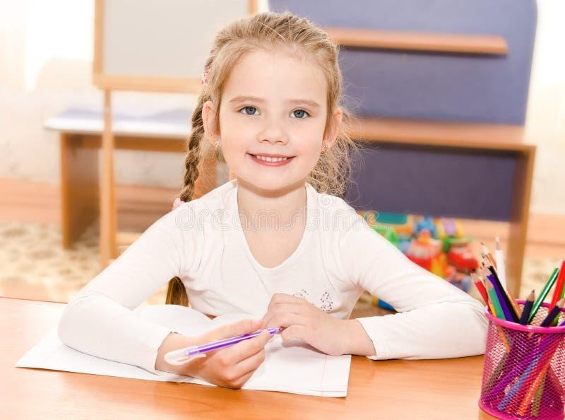 逗人喜爱的微笑的小女孩书写在书桌 库存照片