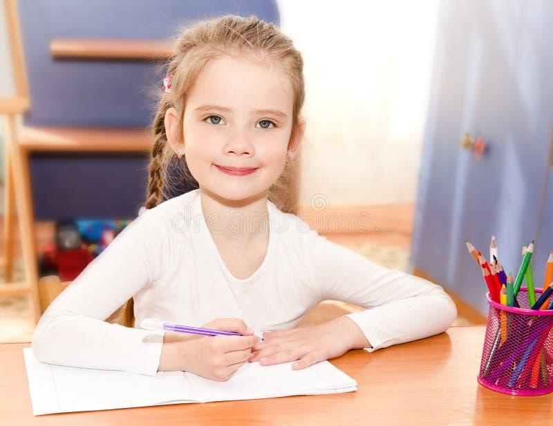 逗人喜爱的微笑的小女孩书写在书桌 库存图片
