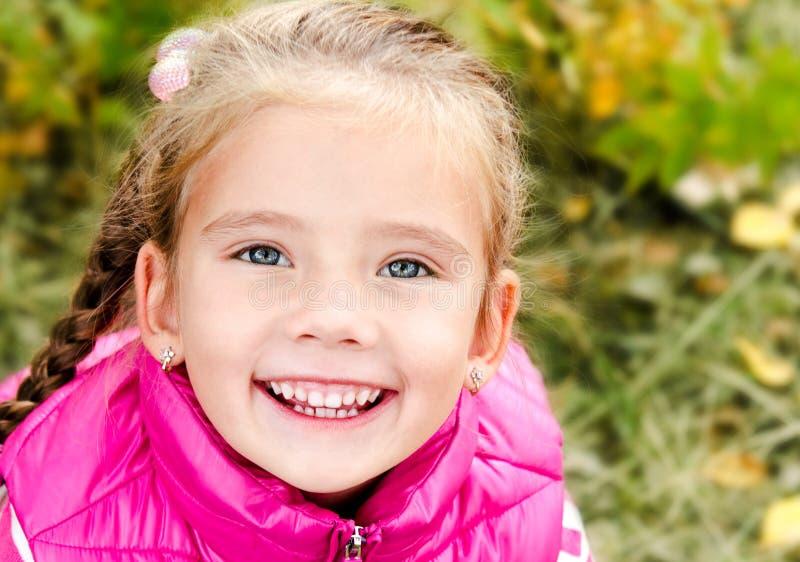 逗人喜爱的微笑的小女孩秋天画象 免版税库存照片