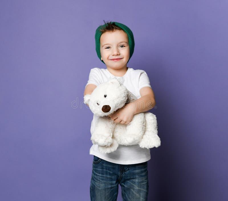 逗人喜爱的微笑的小孩男孩在拥抱他的最好的朋友北极熊玩具的绿色帽子藏品 国际天北极熊概念 免版税库存图片