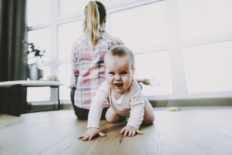 逗人喜爱的微笑的松劲婴孩爬行和的母亲  免版税库存图片
