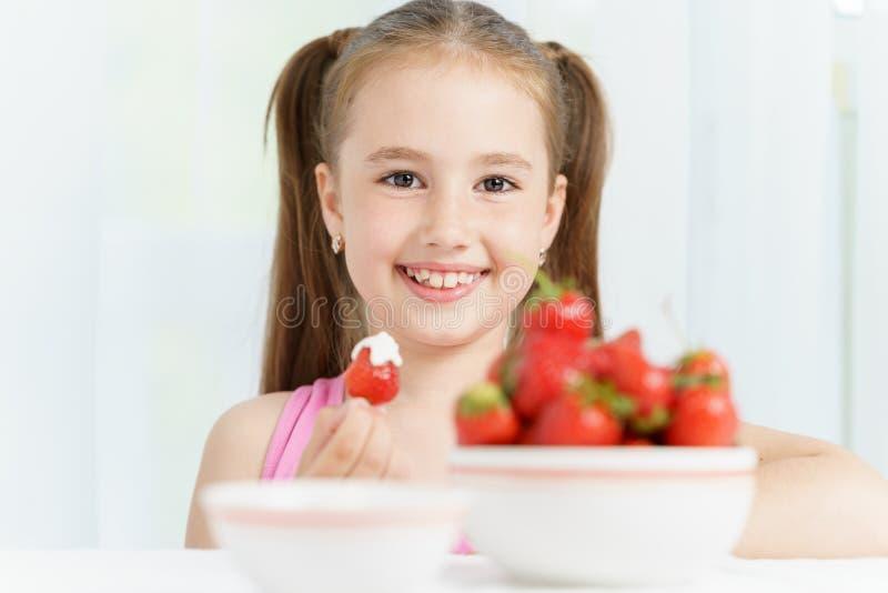 年轻逗人喜爱的微笑的欧洲小女孩吃着与酸性稀奶油的成熟jucy草莓并且拿着许多的白色板材 免版税库存图片