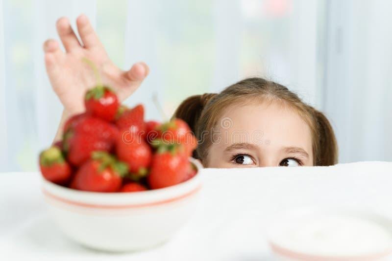 年轻逗人喜爱的微笑的欧洲小女孩设法窃取从许多莓果板材的成熟jucy草莓,当她时 免版税图库摄影