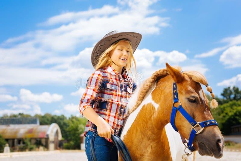 逗人喜爱的微笑的牛仔女孩主导的矮小的美丽的小马 库存照片