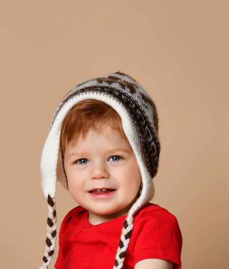 逗人喜爱的微笑的男婴画象被编织的帽子的 免版税库存照片