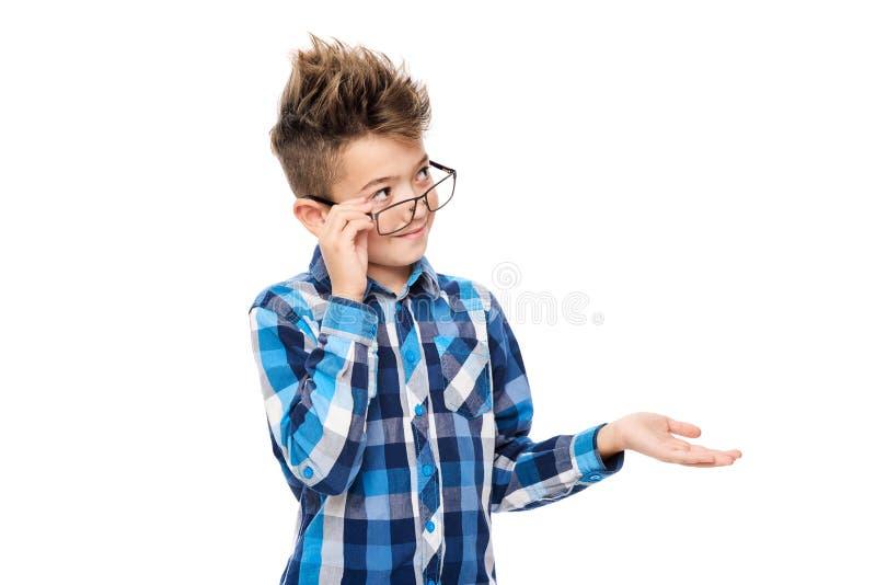 逗人喜爱的微笑的男孩佩带的放大镜和指向用手在白色背景的一张旁边演播室画象 库存图片