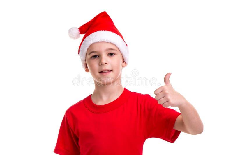 逗人喜爱的微笑的男孩,在他的头的圣诞老人帽子,上升左赞许 概念:圣诞节或新年快乐假日 库存图片