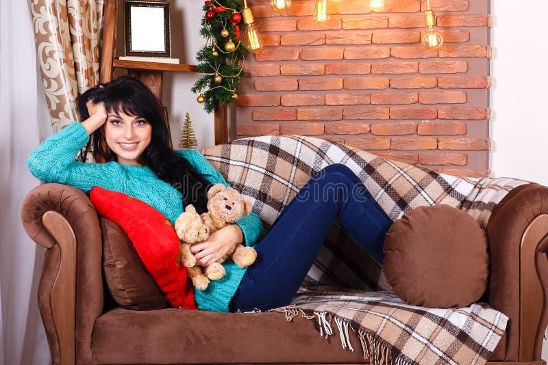 逗人喜爱的微笑的西班牙女孩坐在圣诞节的沙发装饰 库存图片