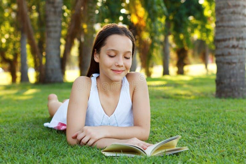 逗人喜爱的微笑的青少年的女孩阅读书 库存图片