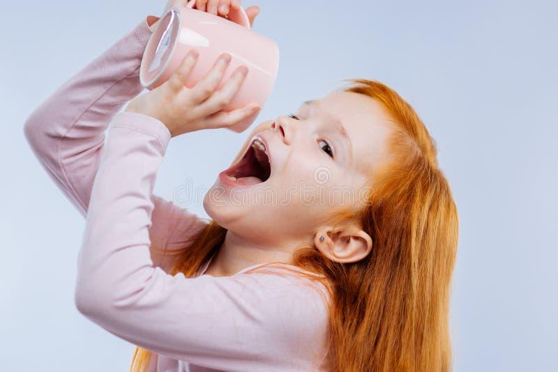 逗人喜爱的快乐的女孩在她的手上的拿着一个桃红色杯子 库存照片