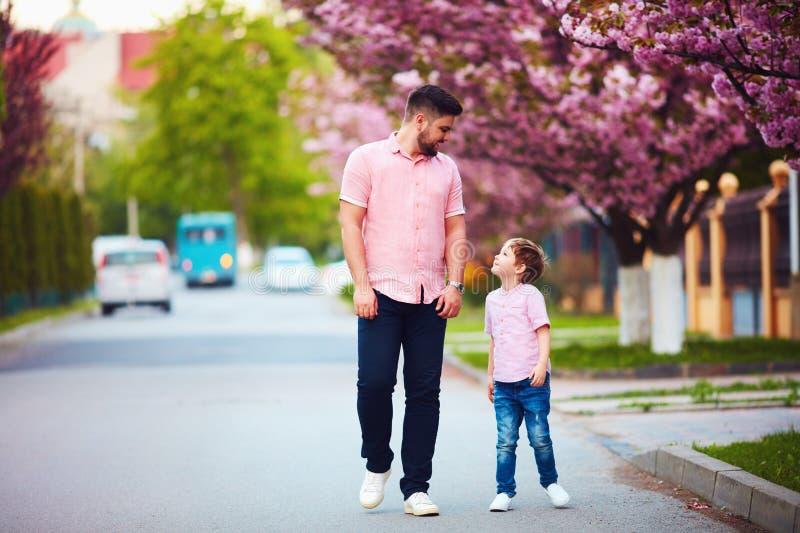 逗人喜爱的快乐的走沿春天街道的父亲和儿子 免版税库存图片