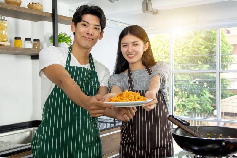 逗人喜爱的愉快的夫妇画象在围裙的在骄傲地提出充满幸福对观众通心面的早餐快乐的行动 图库摄影