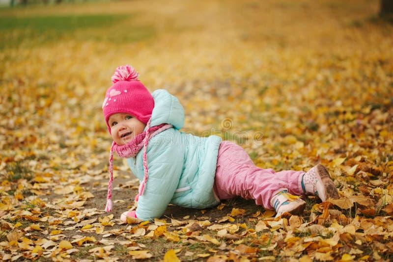 逗人喜爱的愉快的女孩在秋天公园 免版税库存照片