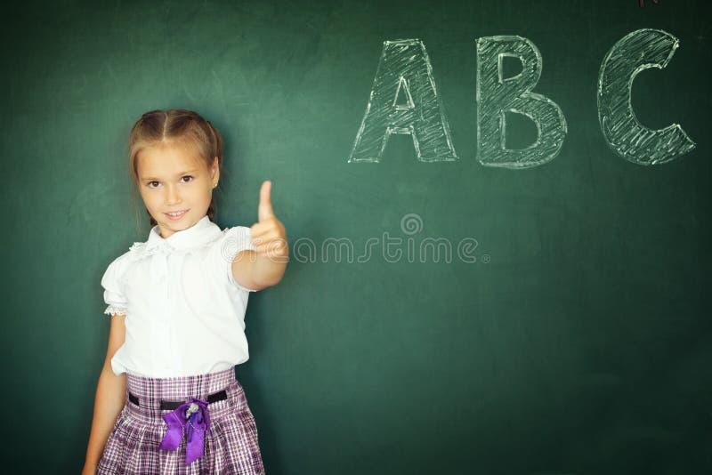 逗人喜爱的愉快的女孩孩子准备好回到学校和显示在绿色黑板背景隔绝的赞许姿态 图库摄影