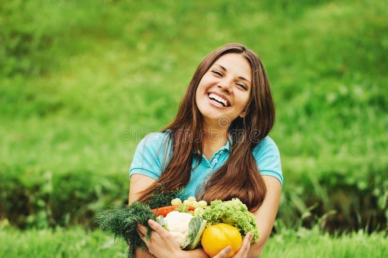 逗人喜爱的愉快的妇女用有机健康水果和蔬菜 库存图片