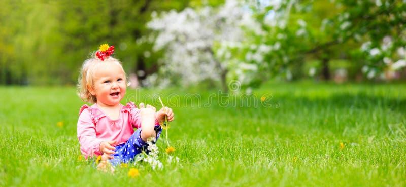 逗人喜爱的愉快的小女孩享受春天自然,全景 免版税库存照片