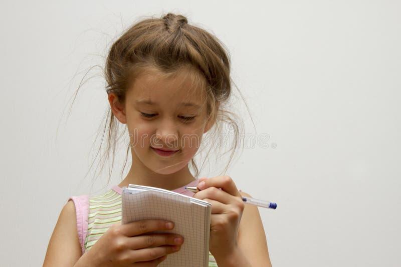 逗人喜爱的愉快的小女孩文字某事在她的笔记本 图库摄影