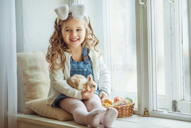 逗人喜爱的愉快的小孩女孩在复活节天佩带兔宝宝耳朵坐少许拿着她的朋友的窗口基石 免版税库存照片