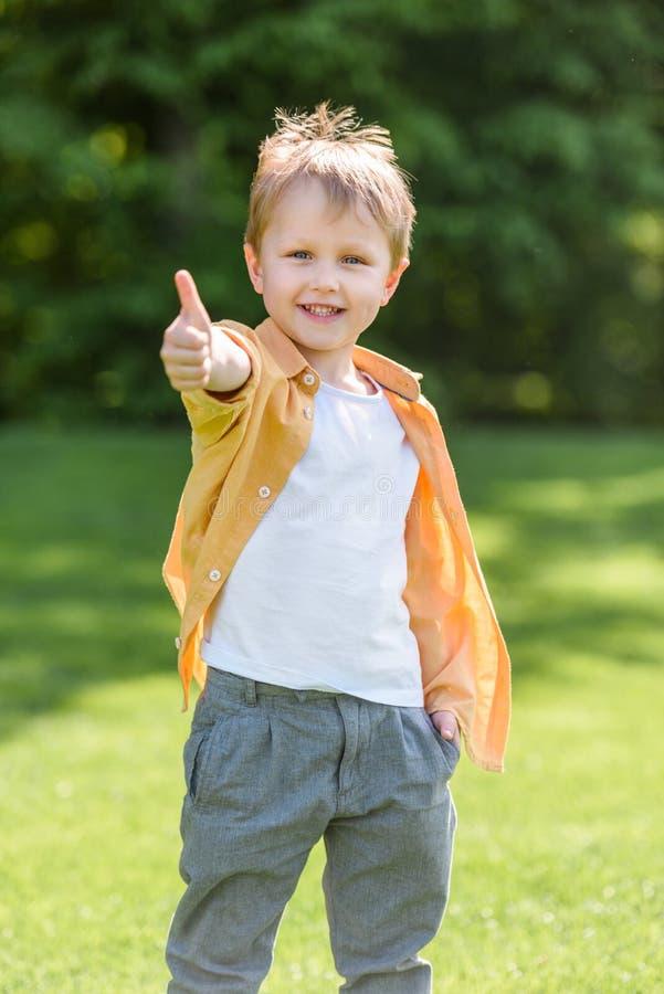 逗人喜爱的愉快的小男孩陈列赞许和微笑对照相机 免版税库存照片