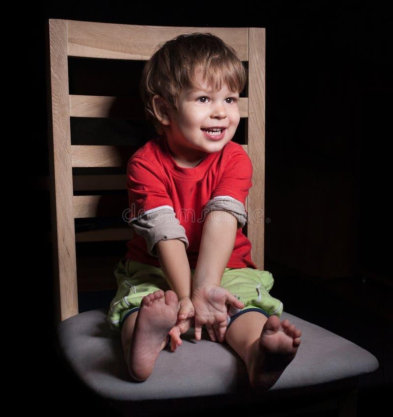 逗人喜爱的愉快的男婴坐椅子 图库摄影
