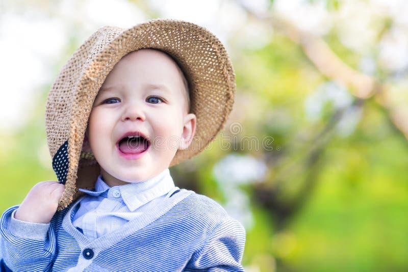逗人喜爱的愉快的白种人男婴在春天公园看照相机 免版税库存图片