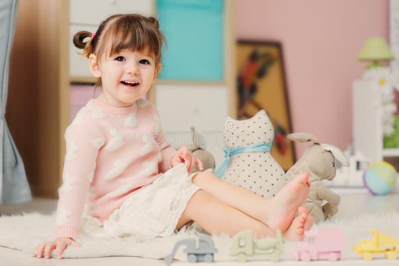 逗人喜爱的愉快的2岁在家使用与玩具的女婴 免版税库存图片