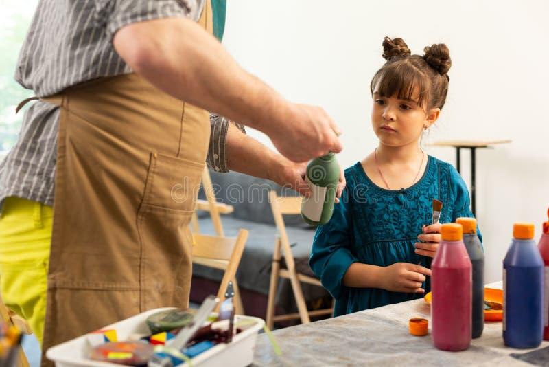 逗人喜爱的打开绿色油漆的女孩等待的老师 免版税库存照片