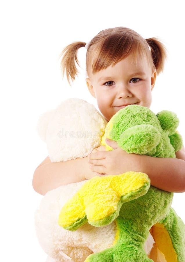 逗人喜爱的拥抱的女孩她软的玩具 免版税库存照片