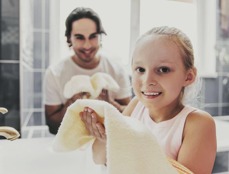 逗人喜爱的拿着毛巾的小女孩和年轻父亲 库存照片