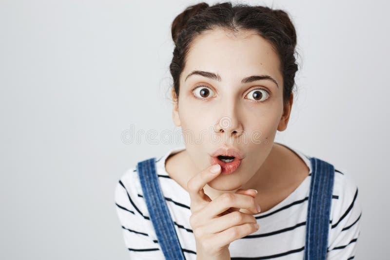 逗人喜爱的时髦妇女特写镜头照片有握在张的嘴的两个小圆面包发型和穿甲的食指和 免版税库存照片