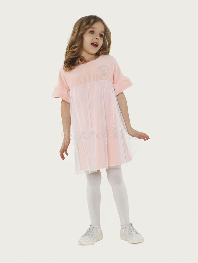 逗人喜爱的有卷发的europeoid白肤金发的女孩画象在桃红色礼服 女孩惊奇 美丽的c 免版税库存照片