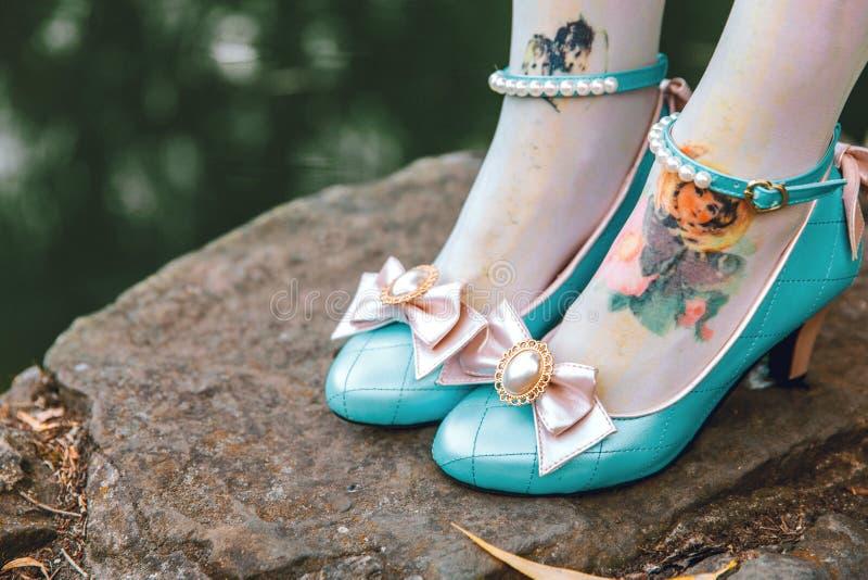 逗人喜爱的有桃红色弓的葡萄酒蓝色鞋子 减速火箭的甜糖果鞋子 免版税库存照片