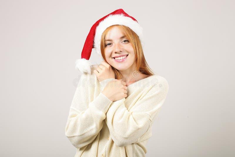 逗人喜爱的有流行音乐pom的红头发人女性佩带的圣诞老人` s帽子,庆祝冬天欢乐季节假日 图库摄影