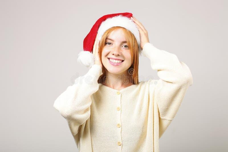 逗人喜爱的有流行音乐pom的红头发人女性佩带的圣诞老人` s帽子,庆祝冬天欢乐季节假日 免版税图库摄影