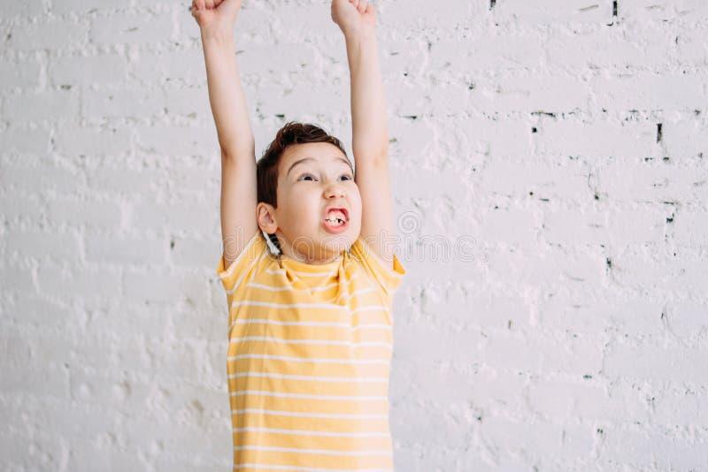 逗人喜爱的有滑稽的面孔的非离子活性剂愉快的胜利男孩在白色砖墙背景隔绝的黄色T恤杉 库存照片