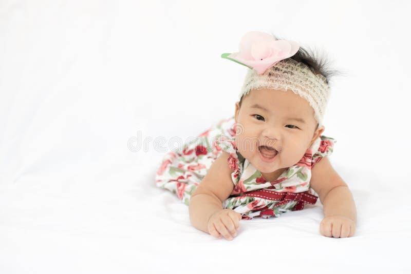 逗人喜爱的有玫瑰色头饰带的婴孩微笑的女孩 免版税图库摄影